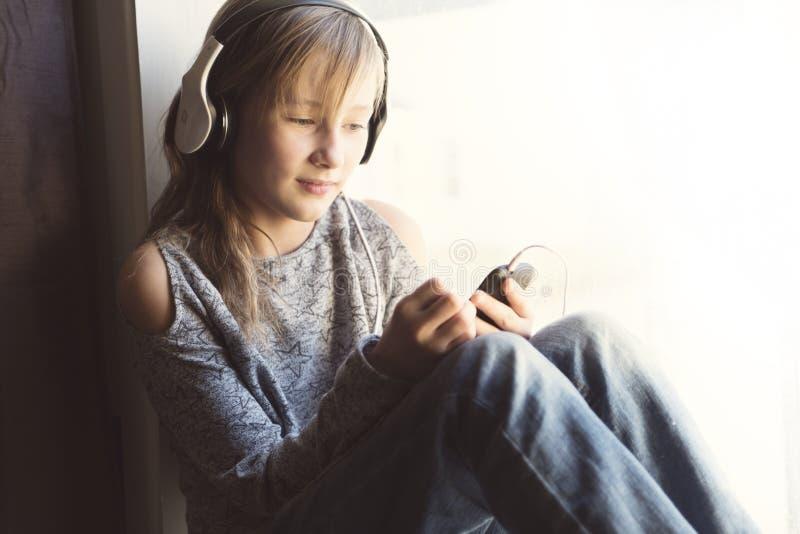 Jonge 10 jaar vrouw het luisteren muziek dicht bij het venster stock foto's
