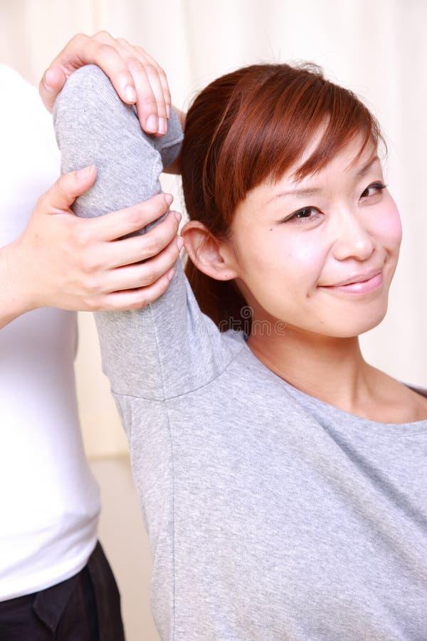 Jonge Japanse vrouw die chiropraktijk krijgen royalty-vrije stock afbeeldingen