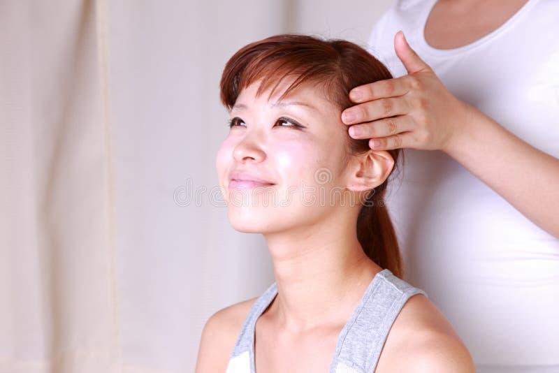 Jonge Japanse vrouw die hoofd krijgen massage  royalty-vrije stock foto