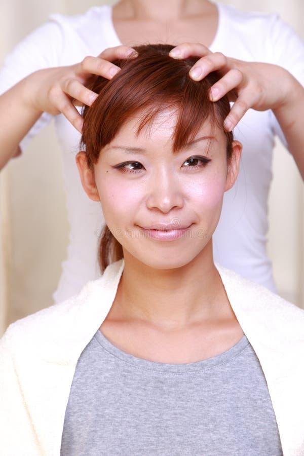 Jonge Japanse vrouw die hoofd krijgen massage  royalty-vrije stock fotografie