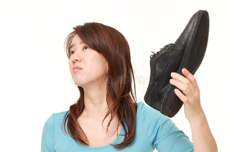 Jonge Japanse vrouw met stinkende schoenen stock afbeelding