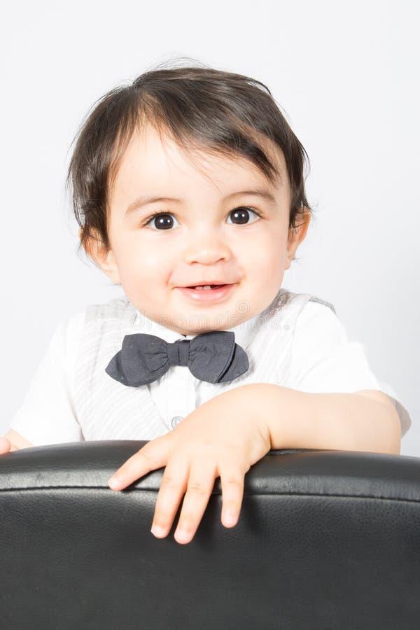 Jonge jong geitjejongen status die op bureaustoel glimlachen stock fotografie