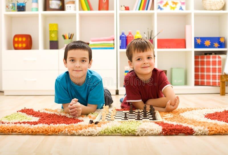Jonge jonge geitjes die schaak voorbereidingen treffen te spelen stock afbeelding