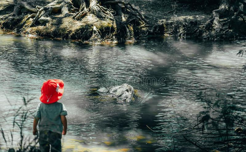 Jonge Jongen bij Voet van de Rivier stock afbeelding