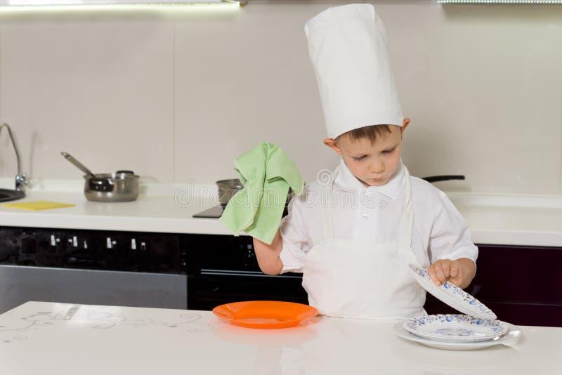 Jonge jongen in chef-koks eenvormige was de schotels stock foto's