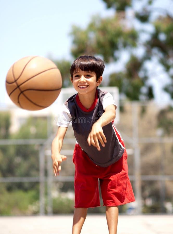Jonge jongen die basketbal overgaat stock afbeeldingen