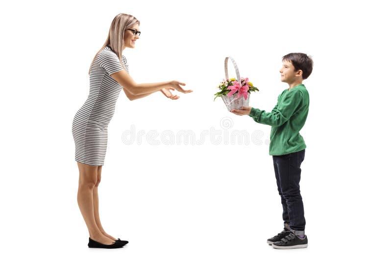 Jonge jongen die bloemen geven aan zijn moeder stock afbeelding