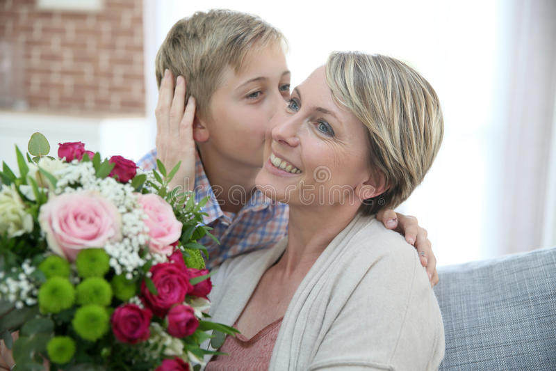 Jonge jongen die bloemen geven aan zijn moeder stock foto's