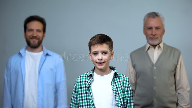 Jonge jongen die camera, op middelbare leeftijd en hogere mensen op achtergrond, steun bekijken stock foto's
