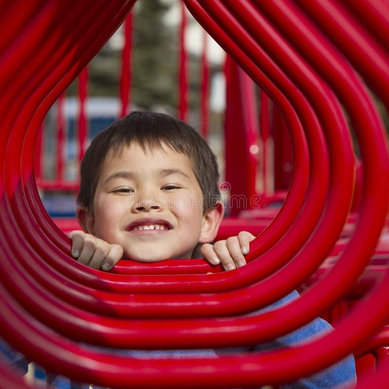 Jonge jongen die in de hoepels van een speelplaats kijkt stock afbeelding