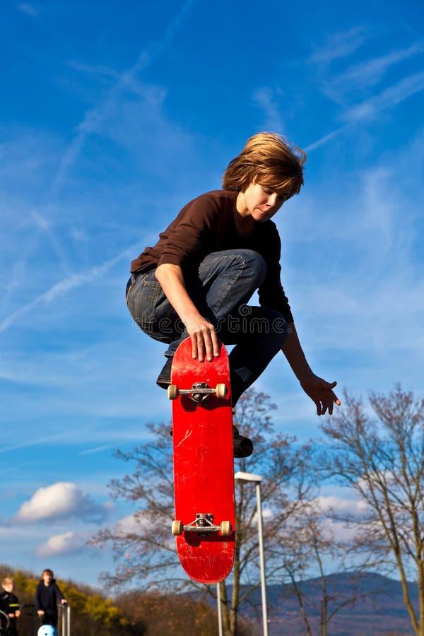 Jonge jongen die in de lucht met zijn skateboard gaat royalty-vrije stock fotografie