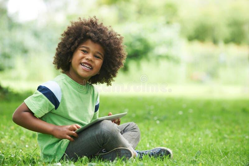 Jonge Jongen die Digitale Tablet in Park gebruiken stock afbeelding