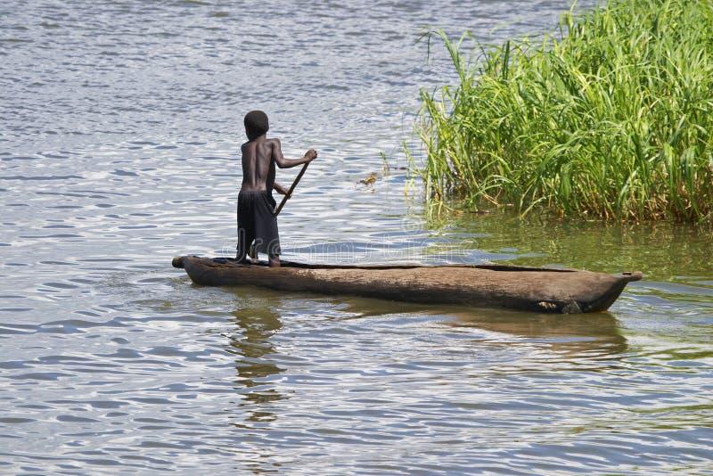 Jonge jongen die dugout in Meer Malawi paddelt royalty-vrije stock afbeeldingen