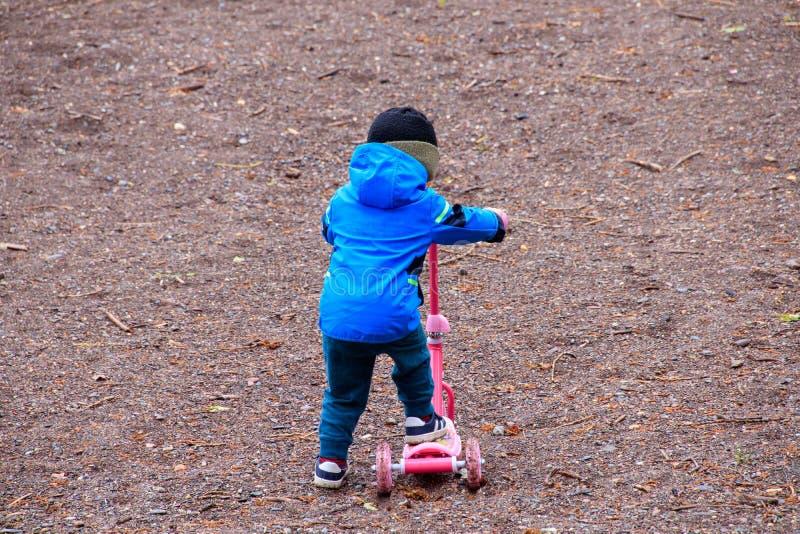 Jonge jongen die een autoped in het grint proberen te berijden stock fotografie