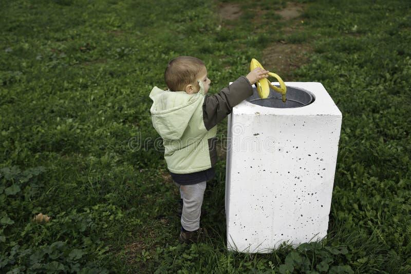 Jonge jongen die een banaanschil werpen in een parkvuilnisbak stock foto's
