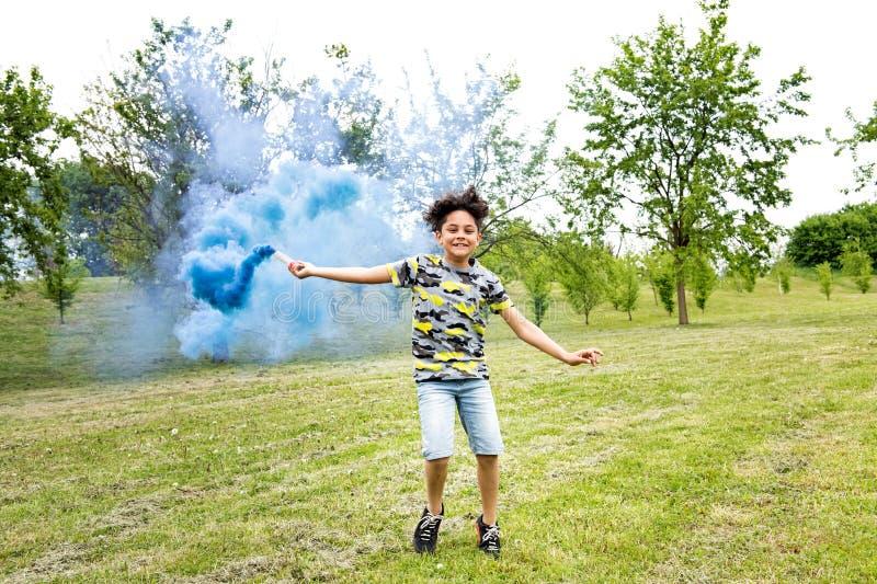 Jonge jongen die een blauwe rookgloed in een park slepen royalty-vrije stock foto
