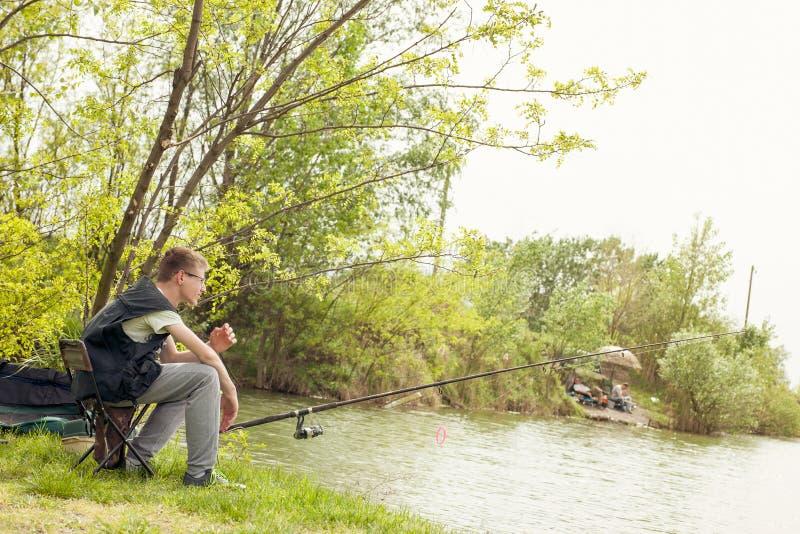 Jonge jongen die in een bosmeer vissen royalty-vrije stock fotografie