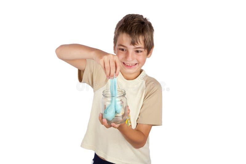 Jonge jongen die een huis gemaakt creëren tot slijmstuk speelgoed royalty-vrije stock foto's