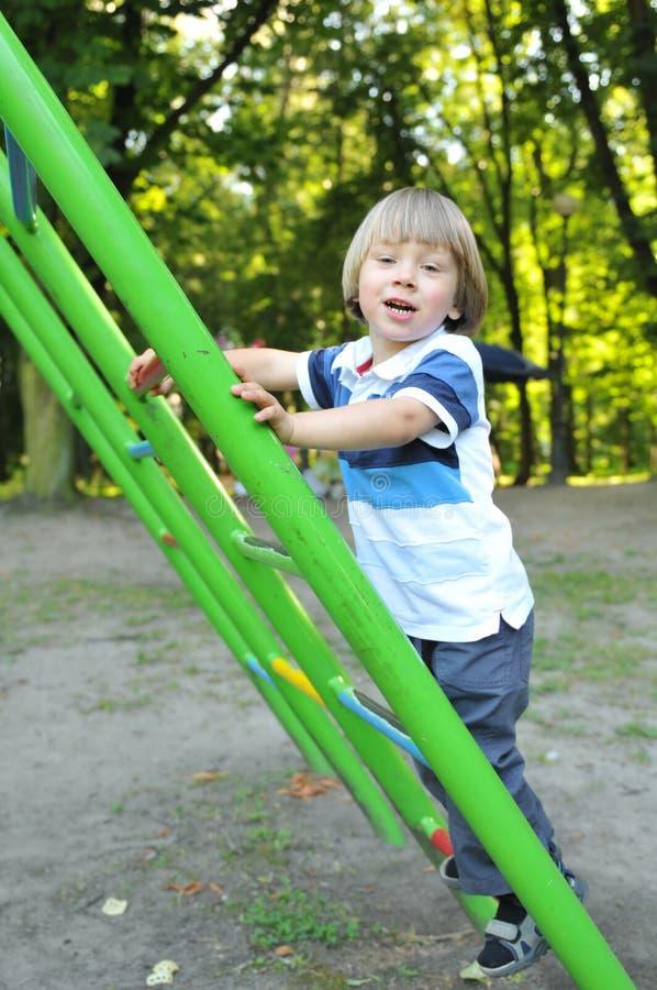 Jonge jongen die een ladder beklimmen royalty-vrije stock foto's