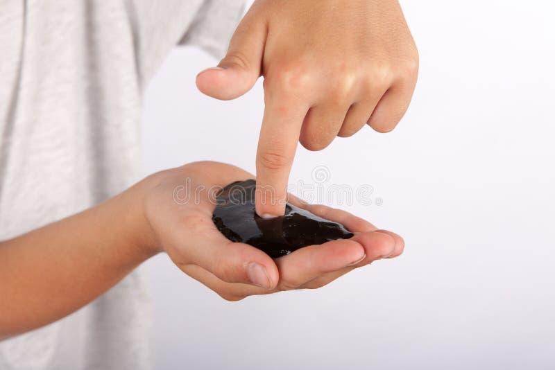 Jonge jongen die een zwart slijm in zijn hand houden stock foto's