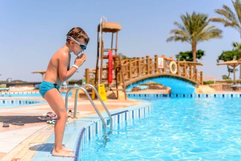 Jonge jongen die in een zwembad voorbereidingen treffen te duiken stock fotografie