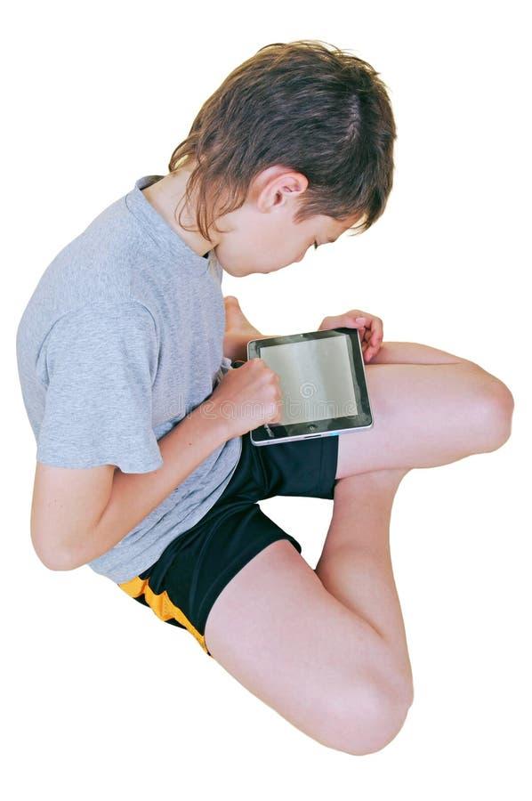 Jonge jongen die elektronische tablet thuis gebruikt stock fotografie