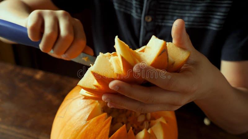 Jonge jongen die en een pompoen snijden schilderen voor Halloween op een lijst stock fotografie