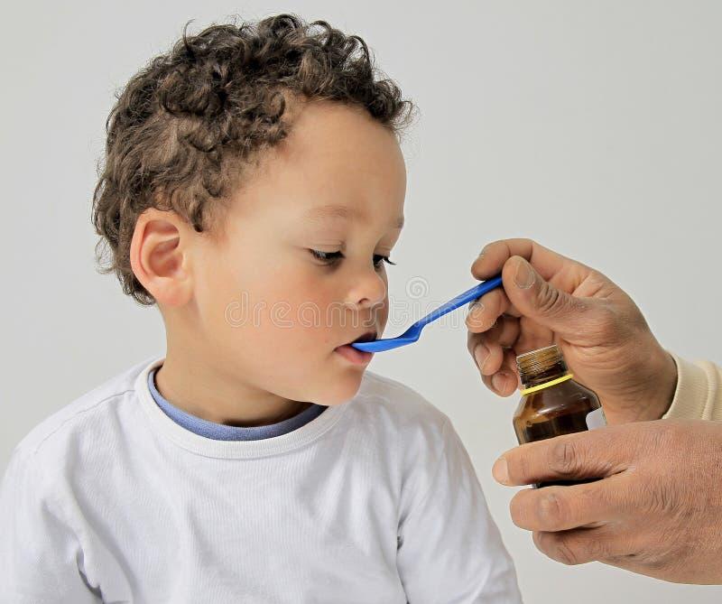 Jonge jongen die geneeskunde nemen stock foto's