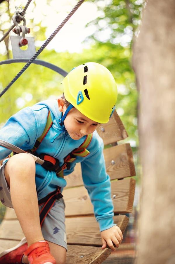 Jonge jongen die kabelroute onder bomen, extreme sport in avonturenpark overgaan royalty-vrije stock foto's