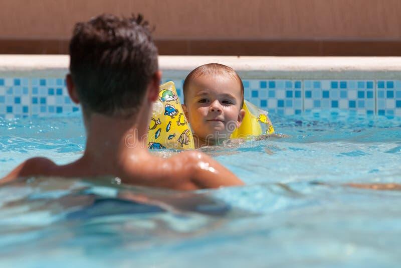 Jonge jongen die leert te zwemmen stock fotografie