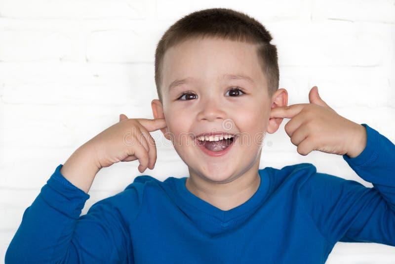 Jonge jongen die matroos met zijn open ogen dragen behandelend zijn oren royalty-vrije stock afbeeldingen