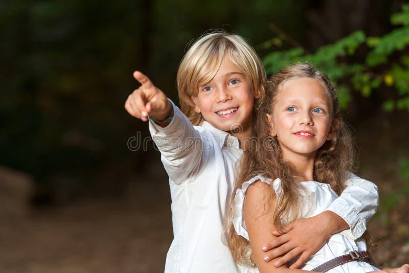 Jonge jongen die meisje de manier tonen. stock afbeeldingen