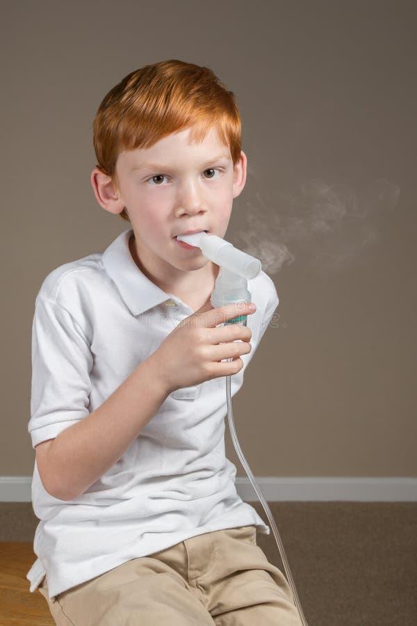 Jonge jongen die met astma een ademhalingsbehandeling voltooien stock foto's
