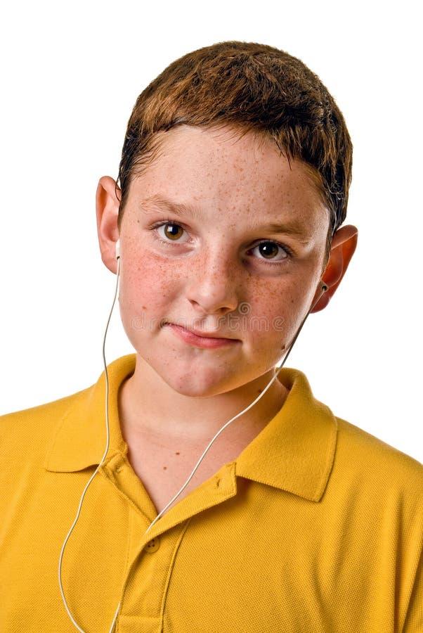 Jonge jongen met earbuds stock foto
