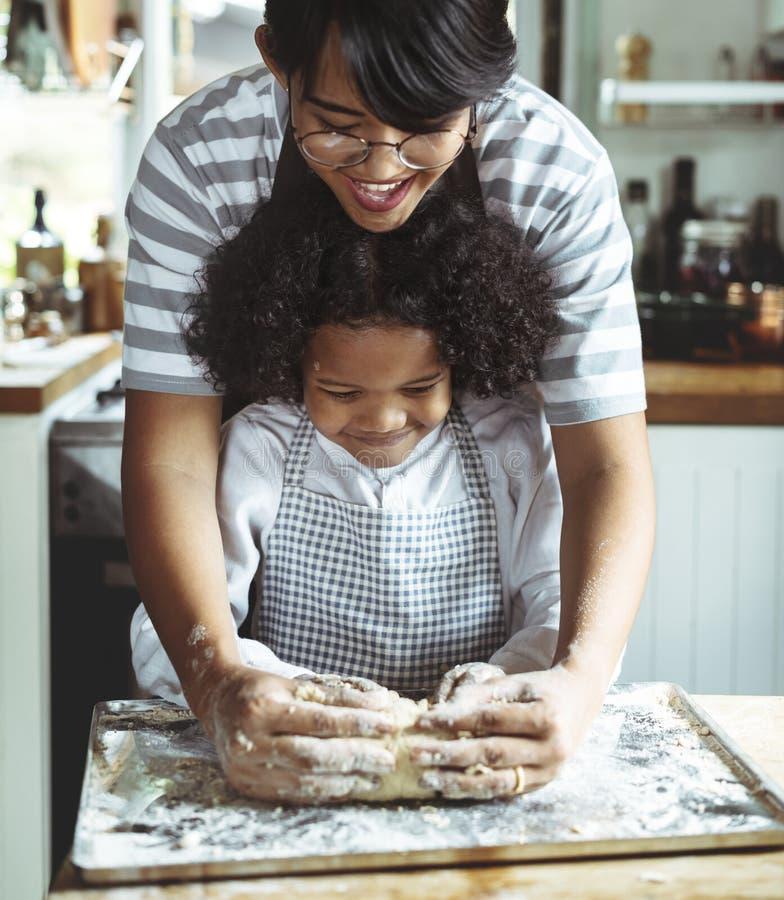 Jonge jongen die met zijn moeder leunen te bakken stock foto