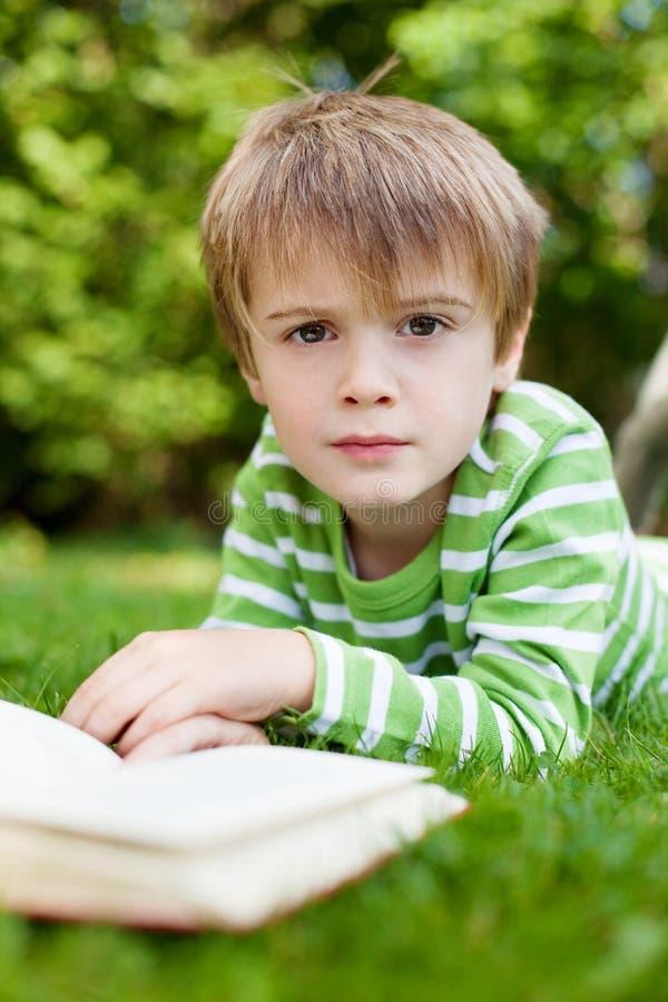 Jonge jongen die omhoog van het lezen van een boek kijken stock afbeeldingen