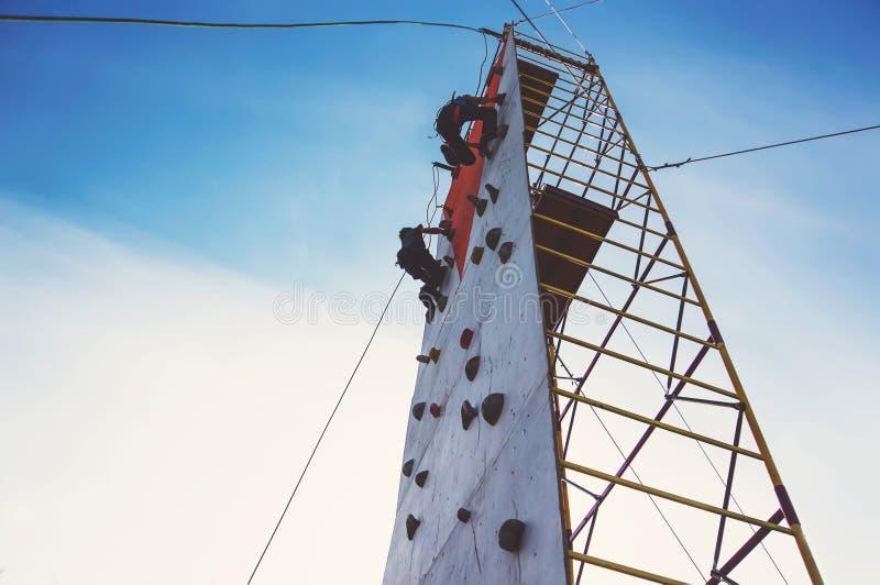 Jonge jongen die op een kunstmatige rotsmuur beklimmen stock fotografie