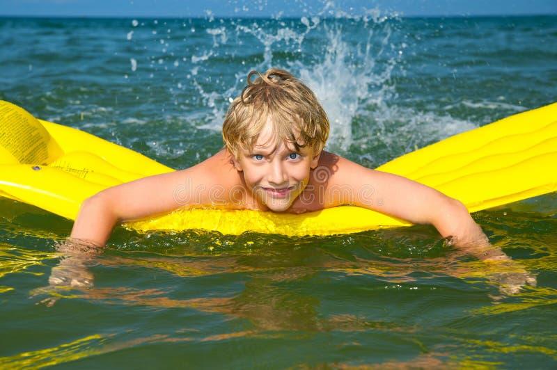 Jonge jongen die op matras in het overzees zwemt stock foto