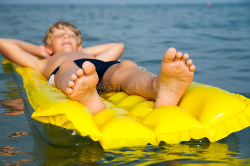 Jonge jongen die op matras in het overzees zwemt stock foto's