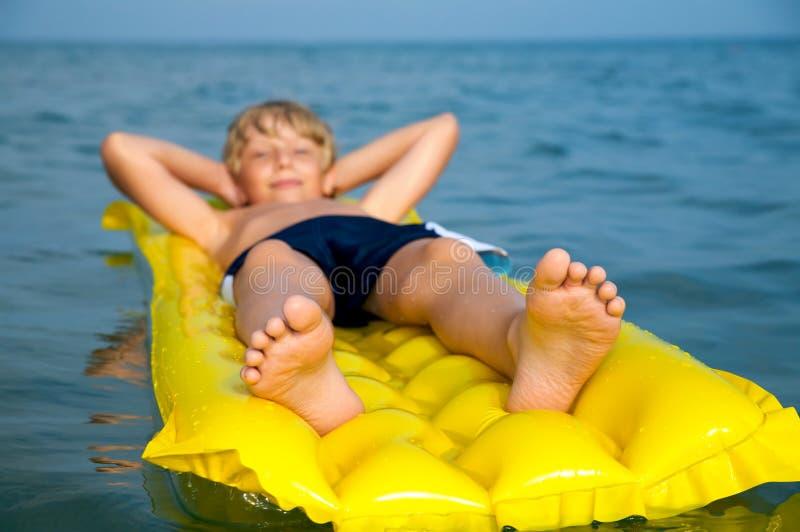 Jonge jongen die op matras in het overzees zwemt royalty-vrije stock fotografie