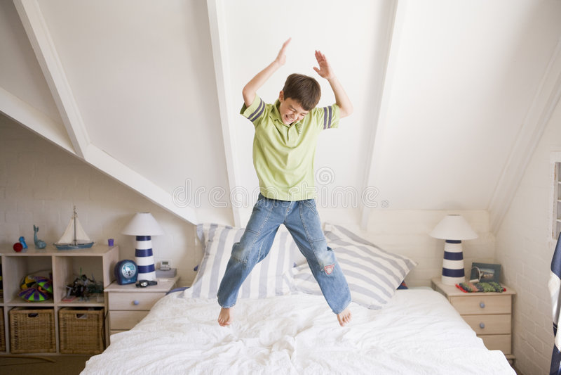 Jonge Jongen die op Zijn Bed springt stock afbeeldingen