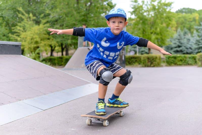 Jonge jongen die op zijn skateboard pronken met stock foto