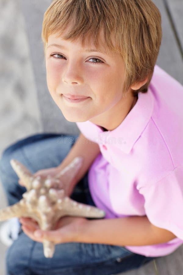 Jonge jongen die in openlucht zeester houdt stock foto's