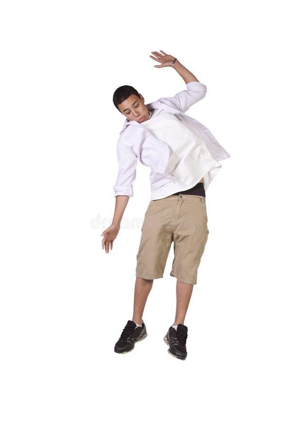 Jonge jongen die over witte achtergrond springen stock foto
