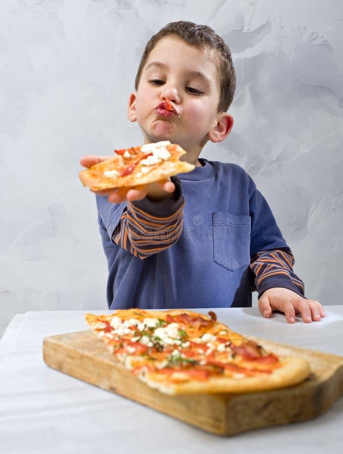 Jonge jongen die pizza eet royalty-vrije stock afbeelding