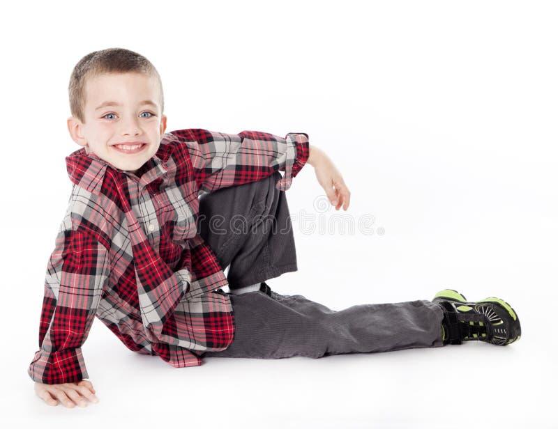 Jonge jongen die in plaidoverhemd aan zijn kant legt stock afbeeldingen