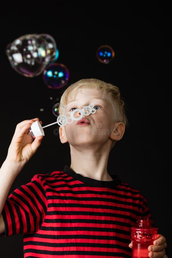 Jonge jongen die pret blazende zeepbels hebben stock afbeeldingen