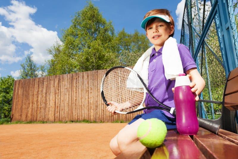 Jonge jongen die rust na het spelen van tennis hebben stock foto's