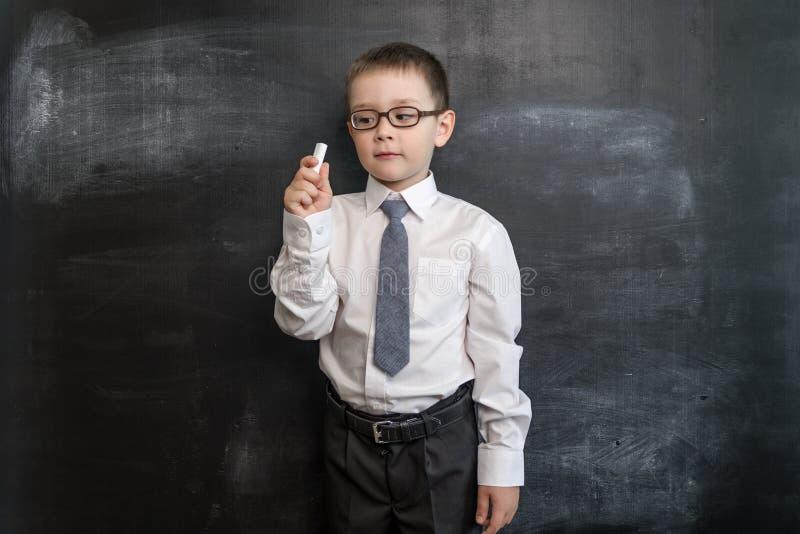 Jonge jongen ` die s een krijt houden dichtbij bord Terug naar het Concept van de School Slimme en slimme peuterjongen stock afbeelding