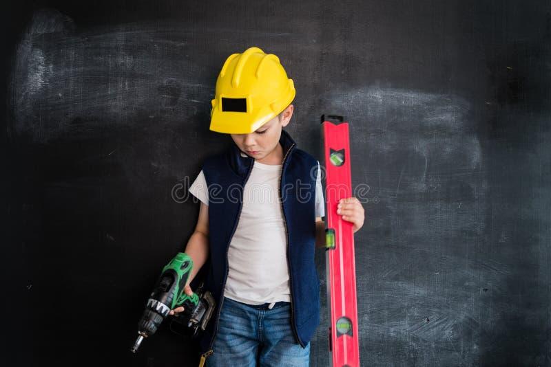 Jonge jongen ` die s zich met schroevedraaier in een helm dichtbij bord bevinden Jonge Bouwer Creatief ontwerpconcept toekomst royalty-vrije stock fotografie
